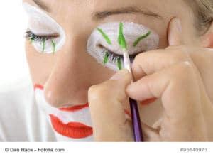 Visagistin oder Maskenbildner schminkt Frau zum Clown